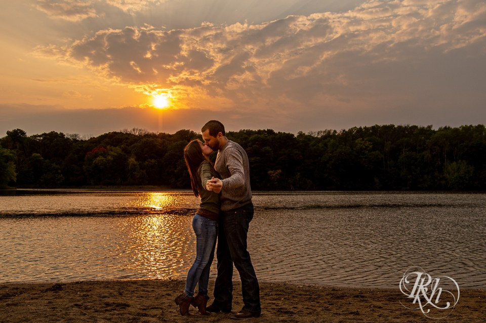 golden hour engagement session couple kissing on beach