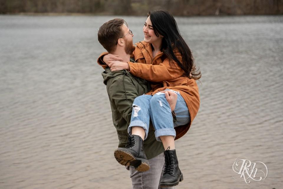 man lifting woman by lake
