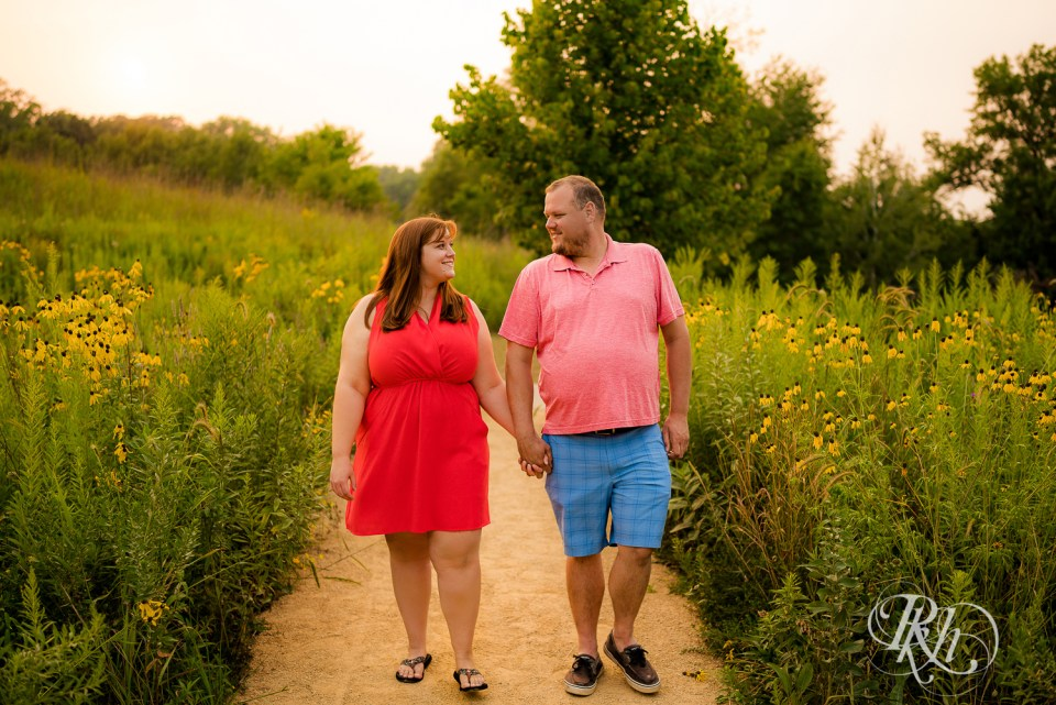 summer engagement photography couple walking in flowers