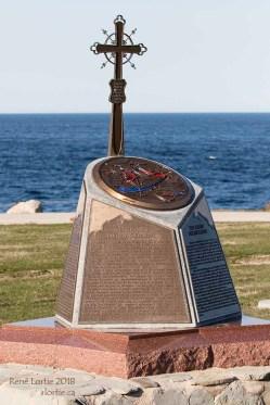 Monument commémorant la déportation des Acadiens de Nouvelle-Écosse surmonté de la croix de Grand-Pré.