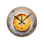Cheesecake on rustic wood cake top. round wall clocks