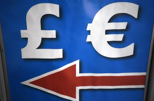 Los símbolos de la libra esterlina (izq) y el euro son expuestos en un cartel en Londres. EFE/Neil Hall/Archivo