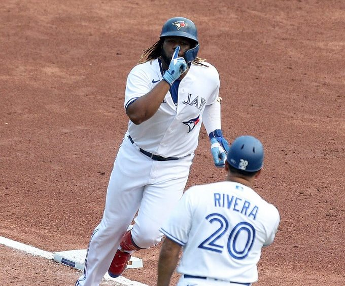 Vladimir Guerrero Jr., #27 de los Toronto Blue Jays, celebra con el coach de tercera base Luis Rivera (#20) al correr las bases tras pegar su jonrón.       (Foto: Bryan M. Bennett/Getty Images/AFP)