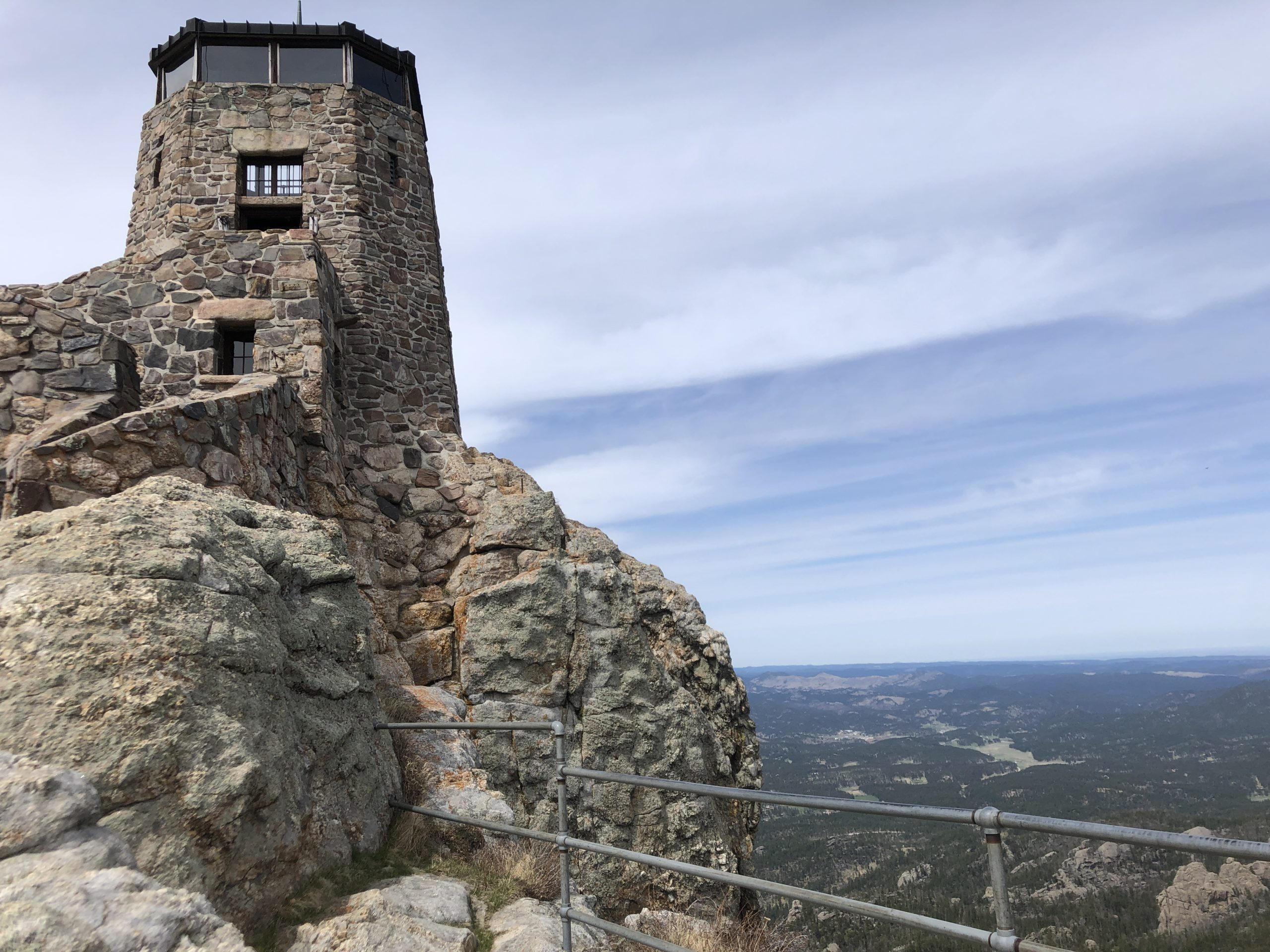 A stone tower atop a mountain overlooking the Black Hills National Forest