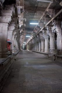 An ancient temple corridor remains silent and eerie in contrast to the bustling streets outside. Kanchipuram, India