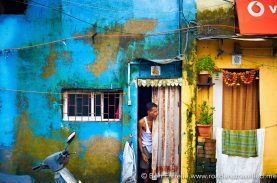 A local man peaks out his curtain door, watching the passing morning chaos. Mumbai, India.