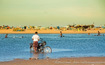 A man washes his motorbike in the tidal sea water. Chennai, India