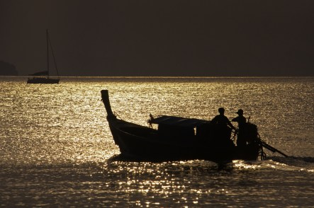 Two fisherman motor out toward the siam sunset. Krabi, Thailand.