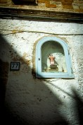 A catholic idol sits in a wall frame on the side of an Italian Villa.