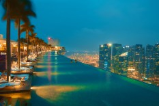 Swimmers swim in the sky overlooking Singapore's financial district at the Marina Bay Sands Hotel. Singapore.