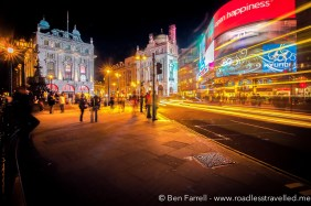 The ever-busy Picadilly Square at night. New meets old as neon signs reflect off the old surrounding buildings. London, England.