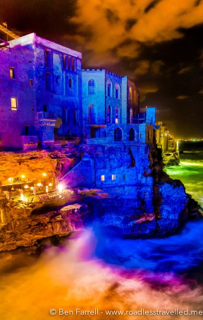 The Adriatic sea dances and crashes against the cliff face lit up by colourful artificial lighting. Polignano a Mare, Italy.