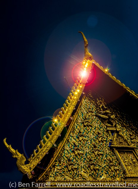 The sun reflects of the intricate mosaics on Thai temple roofs
