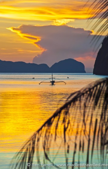 A fishing boat sits idle in the small bay silhouetted by the setting sun.