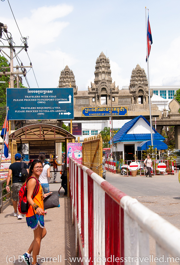 Walking towards the 'Welcome to the Kingdom of Cambodia' stone gateway where the visa building is.