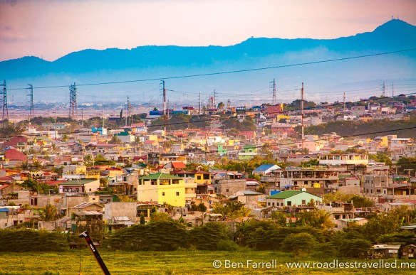 A 'shanty town' lit up by the orange setting sun against the mountains in the distance.