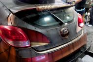 Baseball bat with nails stand ready for use above the rear spoiler