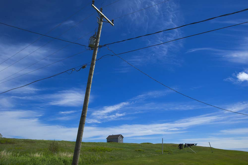 green meadow, a house, blue sky and a hydro pole on the Îles de la Madeleine