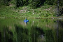 man fishing in mountain lake in blue inner tube boat