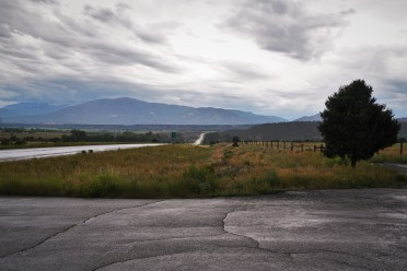 views of highway going through high plain valley with rain clouds