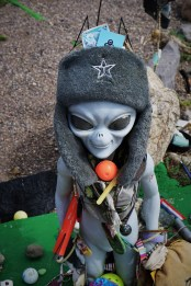 alien statue covered in memorabilia