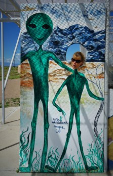 woman poking head through alien photo-op board