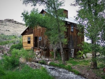 wooden grist mill in front of stream