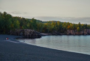 black sand beach at sunset on a lake