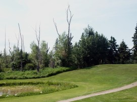 The sole water hazard on the Elk Island golf course is located on the par 3 fourth hole. This photo was taken from the third fairway, looking up towards the tee boxes.
