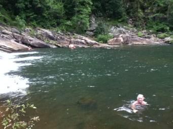 People swimming in mountain pool.