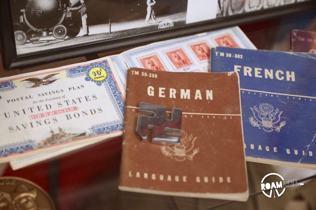 Memorabilia collected while on tour in WWII litters a wall, included mounted displays of swastikas and Nazi memorabilia much like a dears head might be mounted by a hunter.