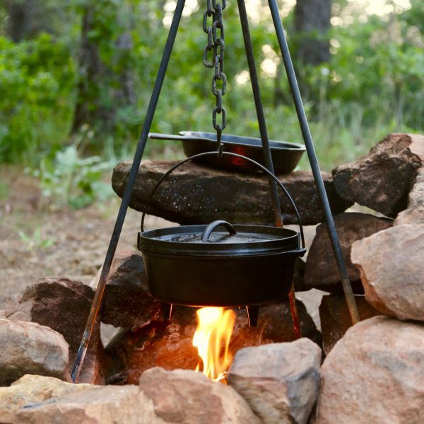Cast iron dutch oven cooking over a campfire.
