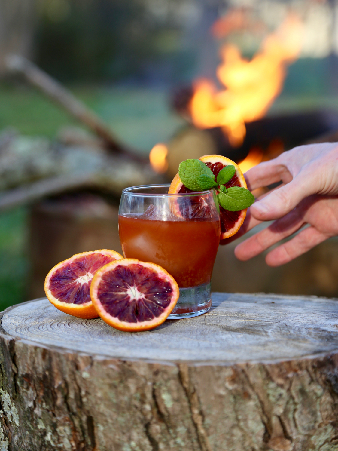Hand reaching for a glass of blood orange cocktail with a fire in the background