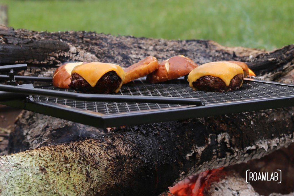 Grilling burgers outside, over a campfire on the Adjust-A-Grill.