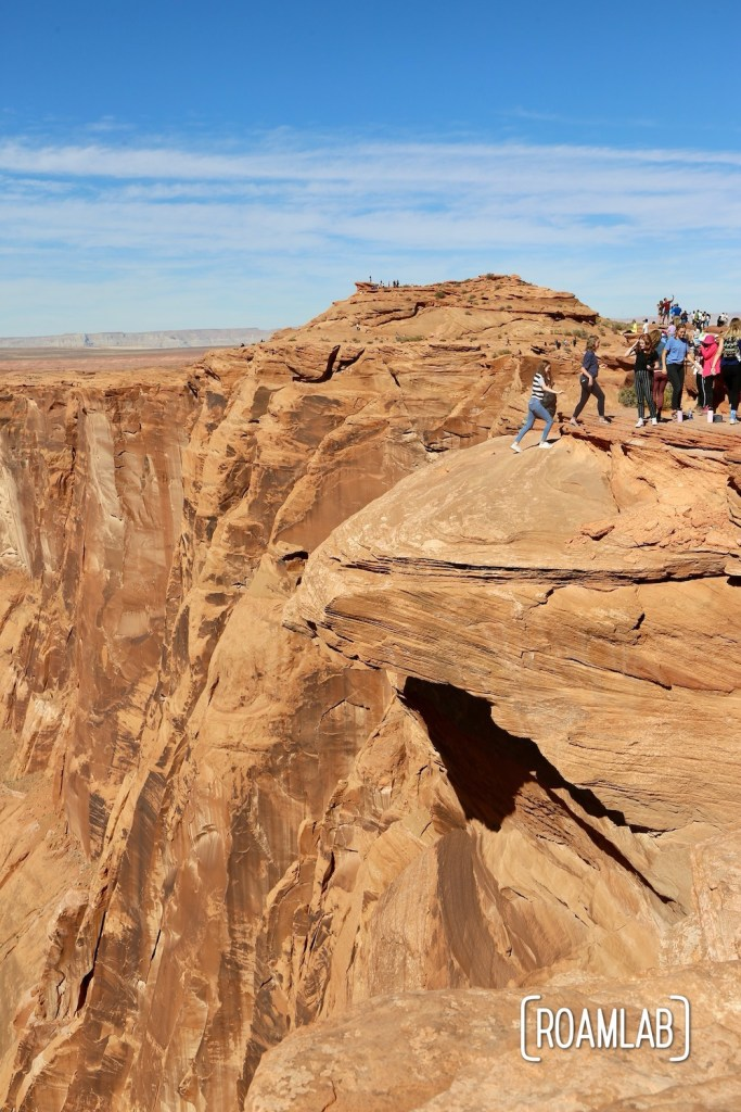Visitors retreating after a picture on a sandstone cliff. They likely didn't see how eroded it is from their perspective.