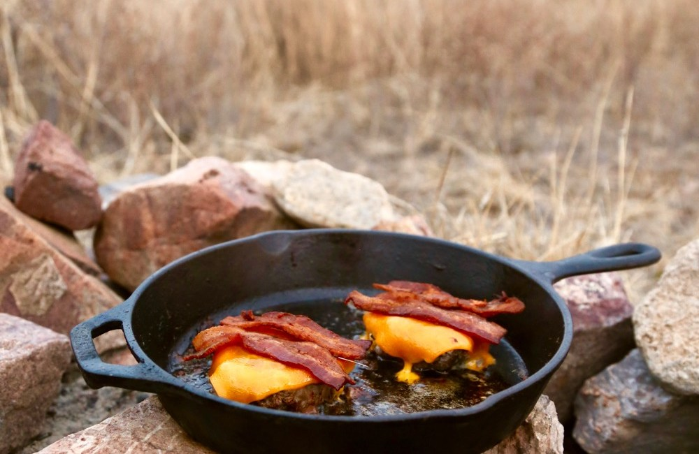 Bacon cheddar cheeseburger on a skillet over the coals.