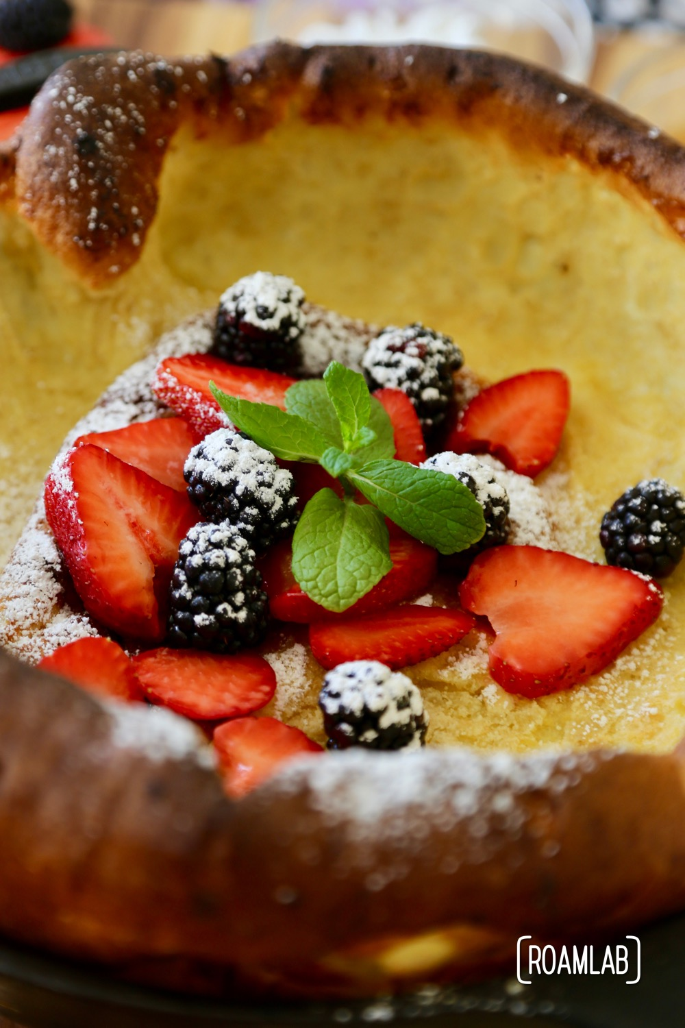 Blackberries, strawberries, powdered sugar and mint on a dutch baby pancake.