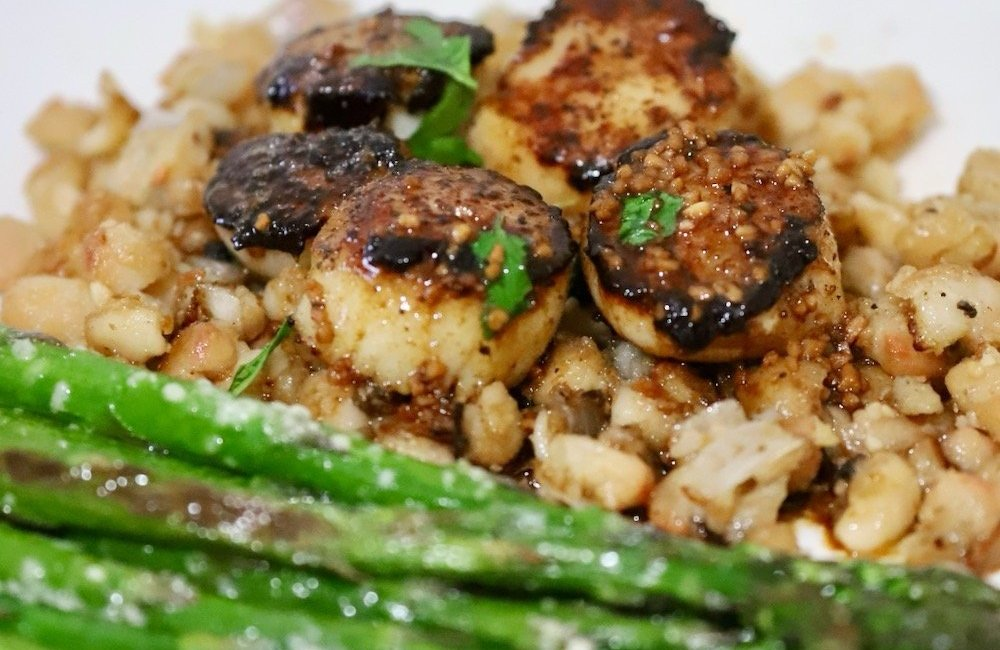 Enjoy this seafood delight of seared sea scallops on a bed of parmesan white beans for a campfire cooking dinner recipe treat from the Roam Lab team.