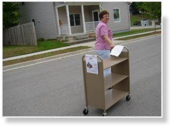A photo of Walking the book carts to the park since the van was too full to transport them along with the used books.