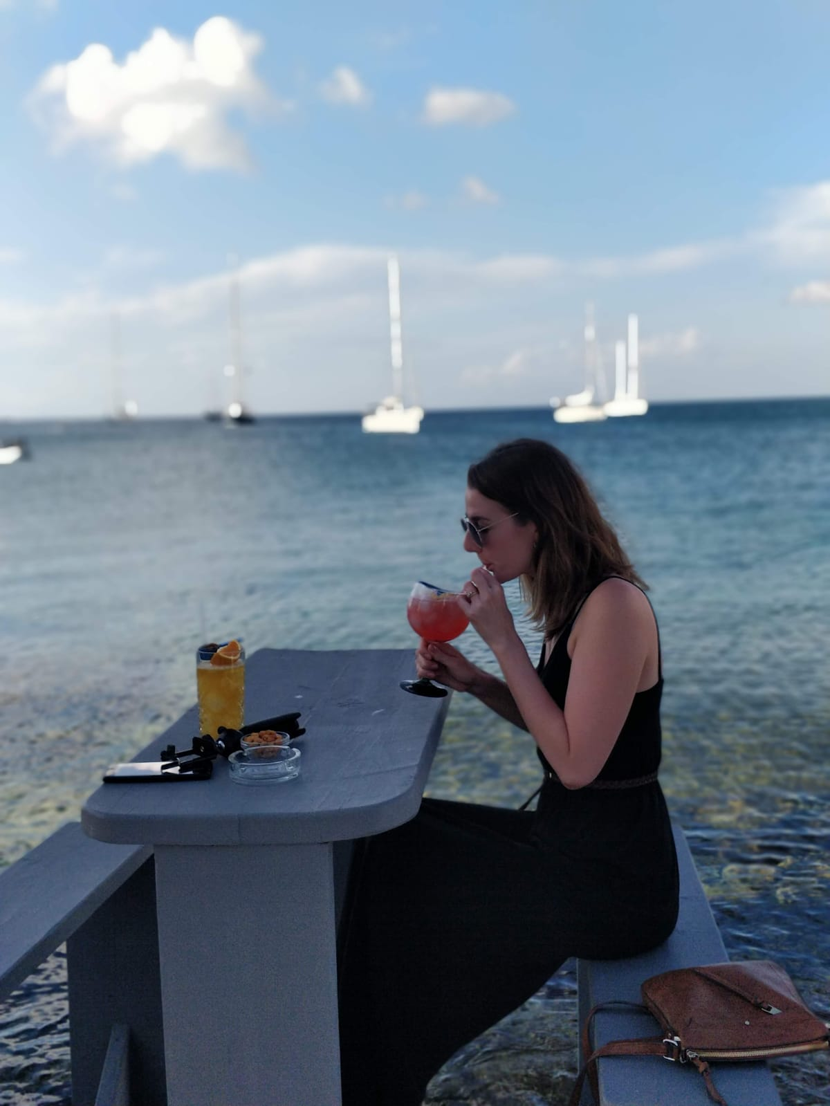 Drink by the sea before dinner - blurred background girl drinks through straw