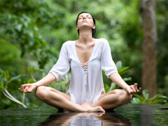 mujer vestida de blanco meditando tranquilamente alrededor vegetacion - Recomendaciones para recibir el equinoccio de primavera