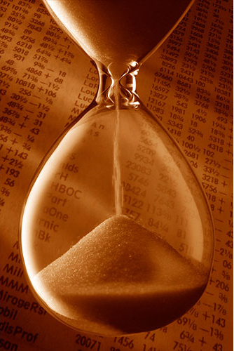 hourglass in front of stock quotes