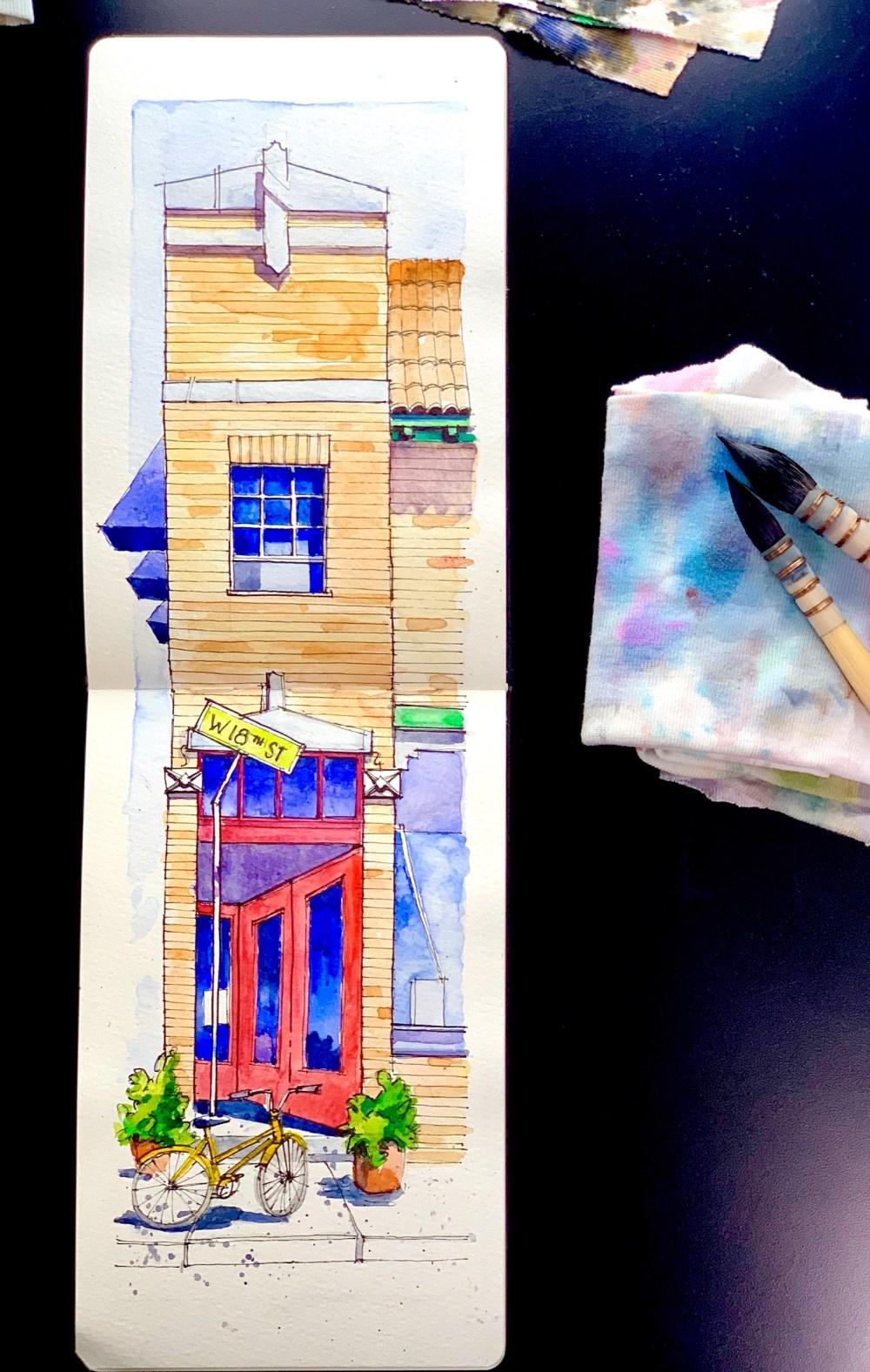 Moleskine Sketchbook over black desk with mop brushes. Brick building with red door watercolor and ink sketch
