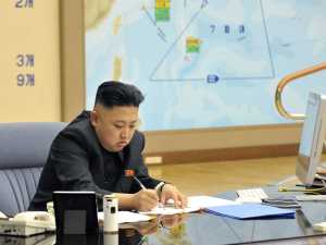 A picture of Kim Jong Un with a iMac on his desk.
