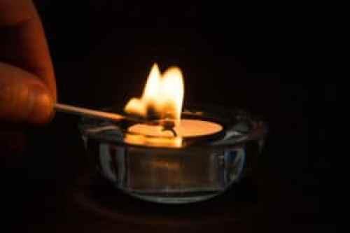 Hand lighting tea light candle in glass holder in the dark