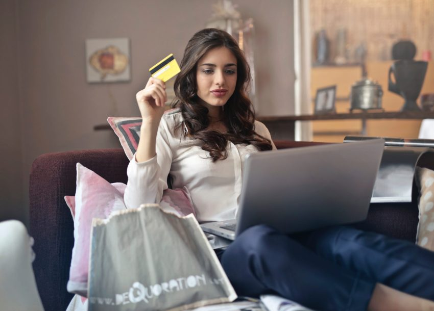 woman holding a card while using her laptop to shop online