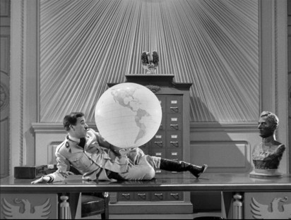 Adenoid Hynkel (Charlie Chaplin) holding a globe of the world.