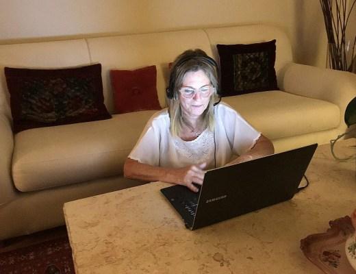 ERAN volunteer Odi Gruber wearing her headset in her Toronto home, where she volunteers taking calls from Israel via her laptop. (Robert Sarner/ Times of Israel)