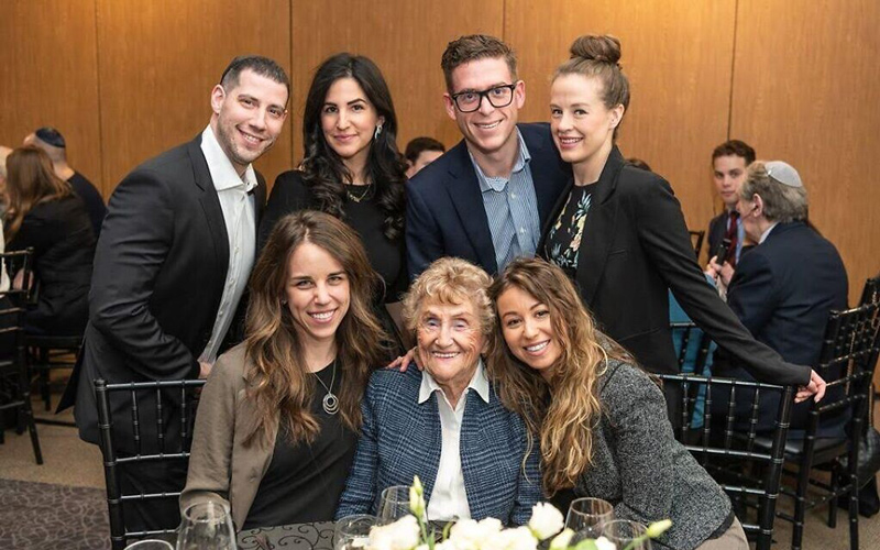 Holocaust survivor Rose Lipszyc, front center, and her granddaughter Brittney Hofbauer, front right, pose with table mates at the Dinner of Miracles in Toronto, December 15, 2019. (Liora Kogan)