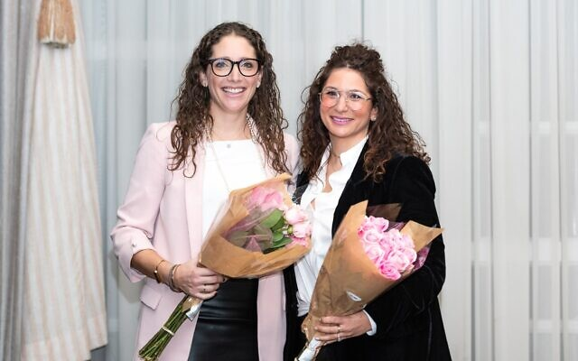 Dinner of Miracles co-founders Sherri Ettedgui, left, and Shawna Samuel receive flowers during a presentation at the Dinner of Miracles in Toronto, December 15, 2019.